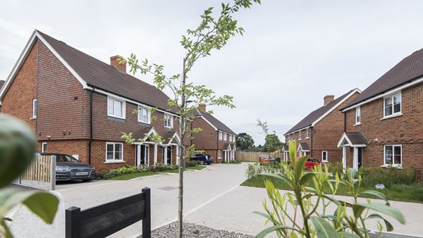 Exterior photo of seven brick houses with gardens and drive parking along a brick paved road