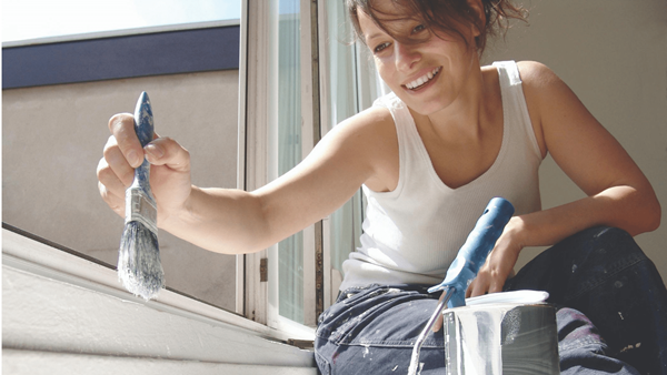 Woman decorating painting a window frame